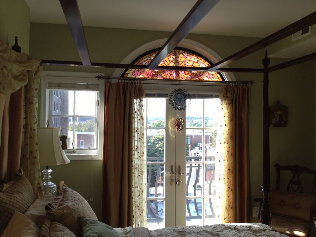 A floral stained glass transom is pictured above the door in a bedroom.
