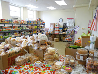 "The ""Distribution Room"" showing food shelves, breads, deserts, fruits and vegetables."
