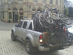 loaded with bicycles silver pickup truck reversing on market