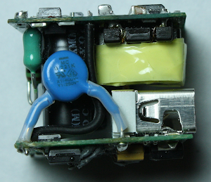 Inside the iPhone charger: input inductor (green), Y capacitor (blue), flyback transformer (yellow), USB connector (silver). The primary circuit board is on top and the secondary board on the bottom.