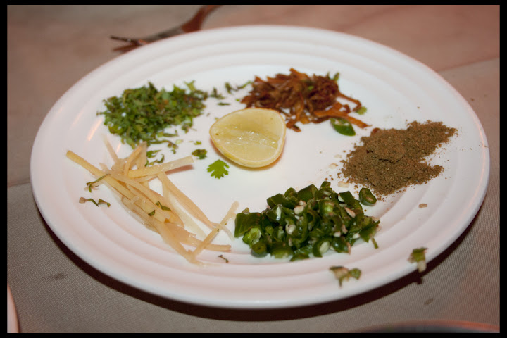 Haleem is accompanied with lemon, ginger, coriander, chillies, brown onion