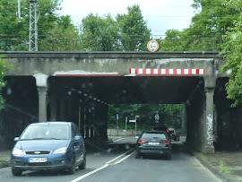 Baufällige Eisenbahnbrücke, darunter Straßenverkehr.