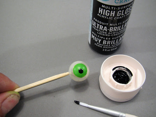 Create a pupil with a dot of black paint.