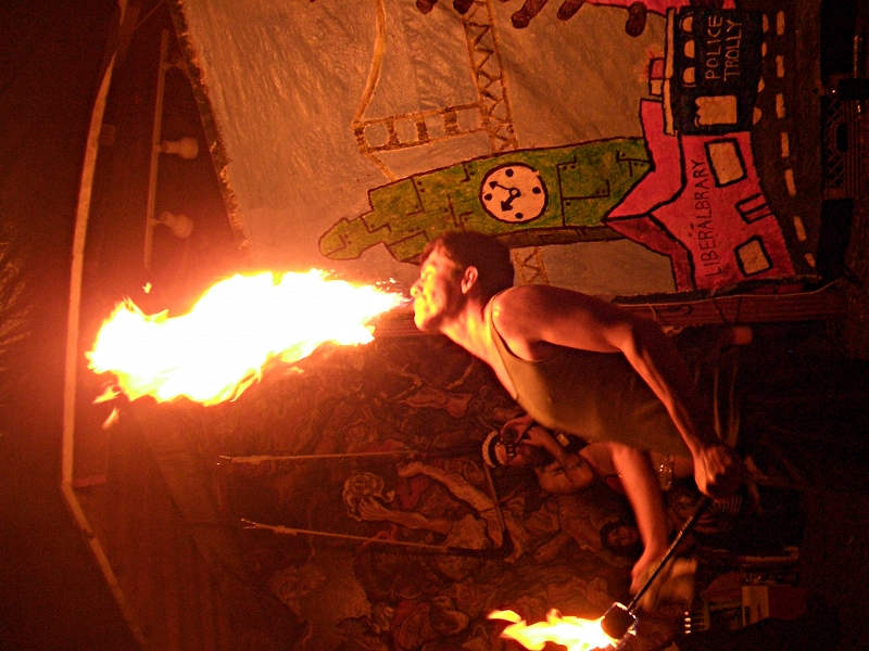A man breathes fire and wields a flaming club in one hand