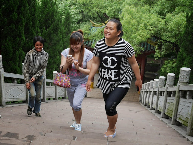 woman in China wearing a shirt with an imitation of Chanel's logo and the word 'FAKE'