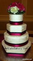 Four tier round and hexagon white fondant wedding cake with royal icing brush embroidery, edible pearls, monogram, curlicues, ribbons and fresh flower topper