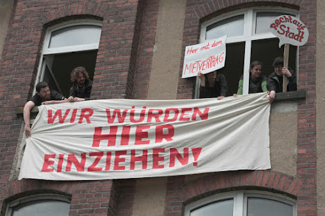 Hausbesetzer mit Transparenten am Haus: »Wir würden hier einziehen!« und »Her mit dem Mietvertrag«.