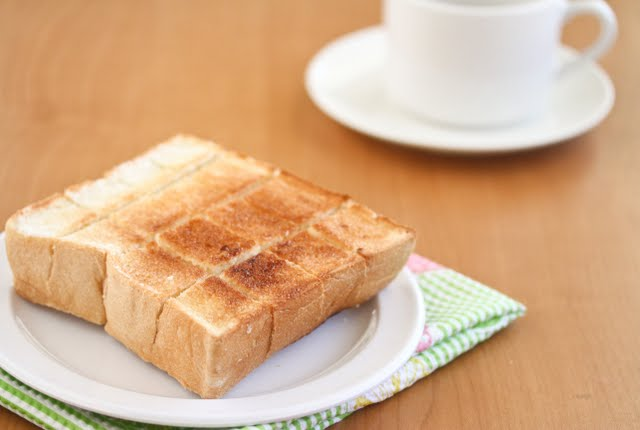 plain brick toast with a white coffee cup in the background