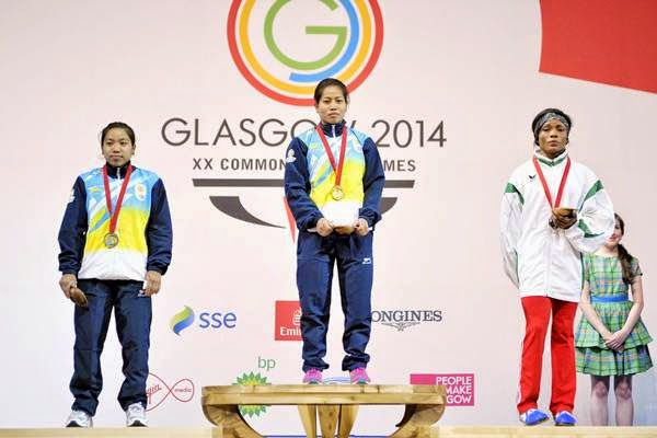 India's silver medalist Mirabai Chanu Saikhom (L), India's gold medalist Sanjita Chanu Khumukcham (C) and Nigeria's Nkechi Opara (R) celebrate with their medals on the podium at the medal ceremony for the women's weightlifting 48kg class at the SECC Precinct during the 2014 Commonwealth Games in Glasgow, Scotland on July 24, 2014.