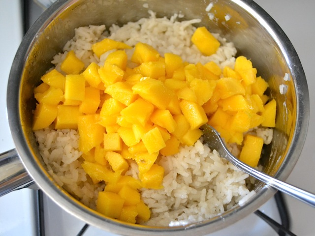 cubed mango added to pot of cooked rice