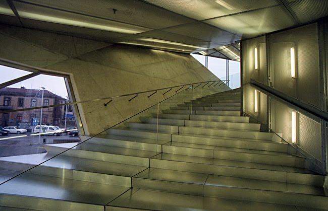 Escadaria em alumínio com separador em vidro. À esquerda uma jnela com vista para a rua