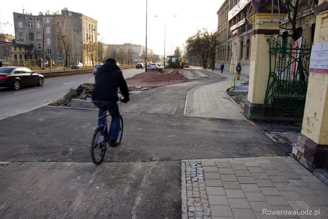 Kierowca wyjeżdżający z tej bramy nie ma prawa dostrzec jadącego rowerzysty... Niestety, drogowcy nie zapewnili wyniesionego przejazdu.