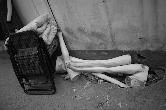 folded chairs, blankets, and broken mannequin legs on a street in Changsha, China