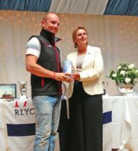 J/70 sailor R. Scott accepting award at Cowes Week Short Series