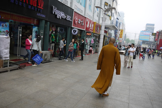 monk walking on a pedestrian street