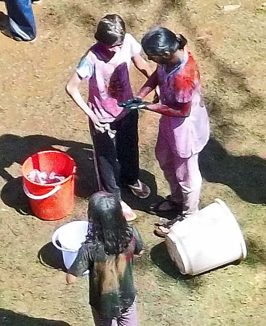 girls mixing colors during Holi
