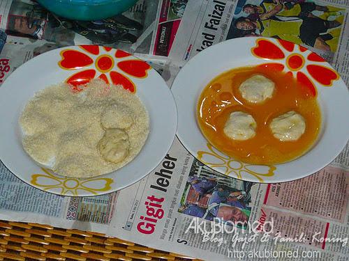 Nugget ikan dicelup dalam telur sebelum ditabur serbuk roti