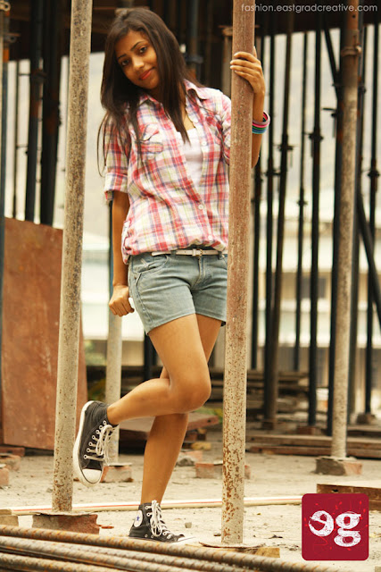 Shorts, button down check shirt folded till the elbow, fitting converse, thin belt and few colourful wooden bangles.