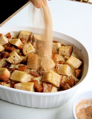 sugar being sprinkled onto the bread pudding