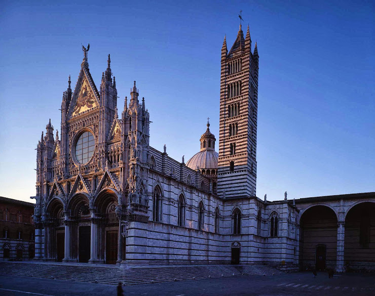 The richly decorated facade of Siena's cathedral at golden hour
