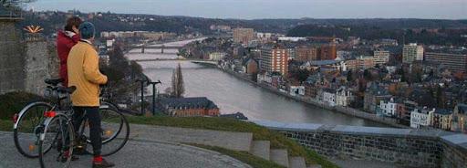 Bruselas Valonia: pareja dando un paseo en bicicleta contemplando la ciudad y el río desde la parte alta de la ciudad