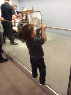toddler climbing up to see an exhibit at the science museum