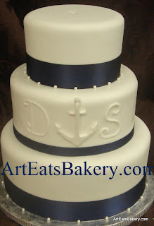 Three tier white fondant wedding cake with navy blue ribbons, sugar pearls, anchor and initials