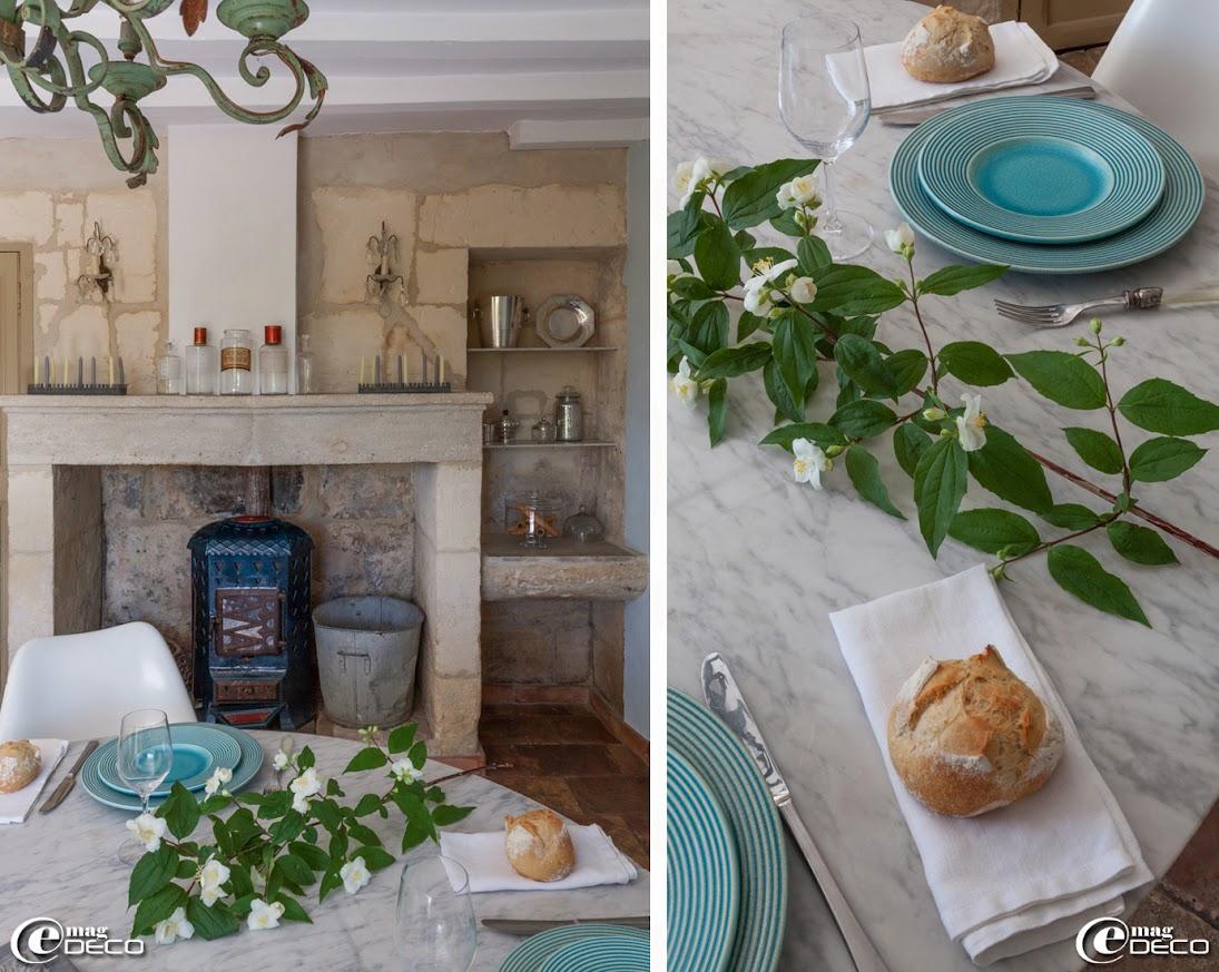 Dans la cheminée d'un mas provençal rénové est installé un vieux poêle en fonte, bonbonnière en verre 'P'Home d'Amour' et bocal 'Bloomingville'