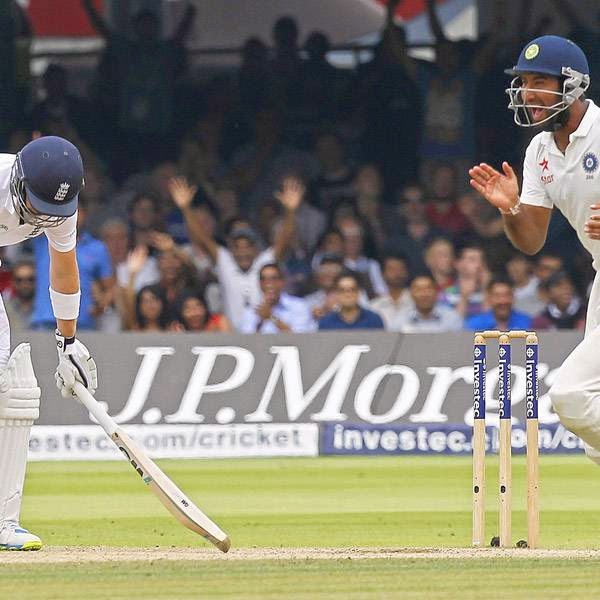 India's Cheteshwar Pujara (R) celebrates after England's Joe Root (L) is caught out by India's Stuart Binny (not pictured) for 66 runs on the fifth day of the second cricket Test match between England and India at Lord's cricket ground in London, on July 21, 2014.
