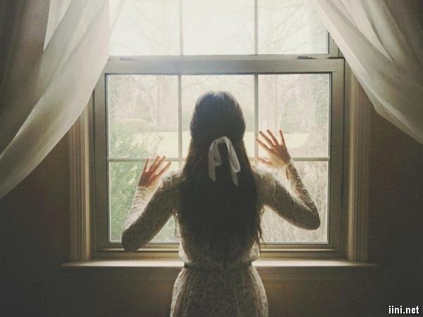 ảnh cô gái buồn đứng ở cửa số nhìn ra ngoài