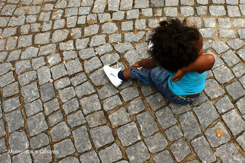 Menina sentada na calçada