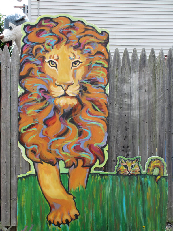Lion and domesticated cat walking through high grass side by side.