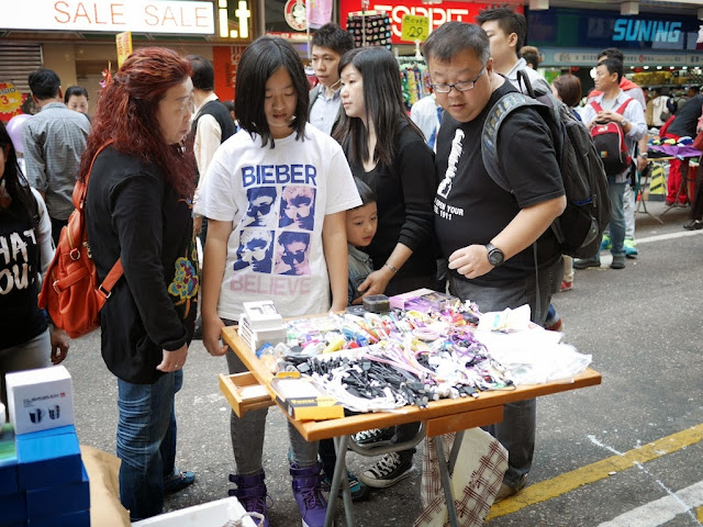 young woman wearing a Bieber shirt looking at items for sale at Sai Yeung Choi Street South
