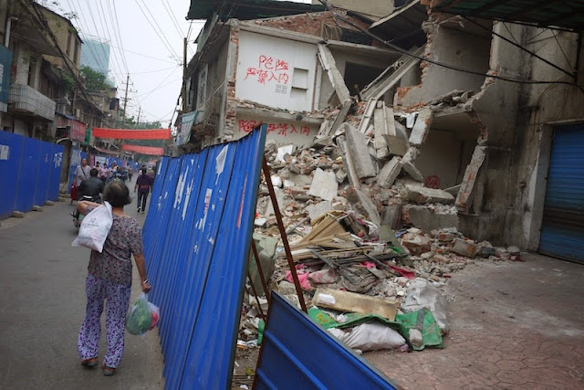 woman carrying bags next to a demolished building at Beizheng Street in Changsha, China