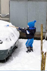 Un bimbo mentre tenta di eliminare la neve dall'auto di papà (foto Elite)