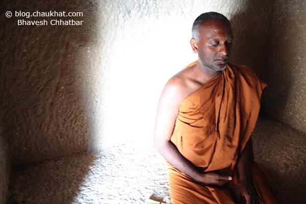 A monk in the state of deep withinself looking for inner peace through meditation at Bedse Caves
