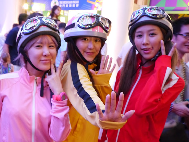 three young women wearing racing clothes, helmets, and goggles in Macau