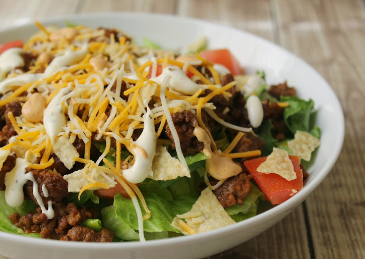 Quick & Easy Taco Salad Recipe with seasoned ground beef, romaine lettuce, diced tomatoes, crushed tortilla chips, shredded Mexican blend cheese, and drizzled with ranch dressing and ranchero sauce