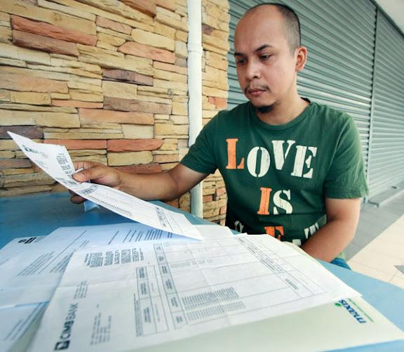 WAN ISMAIL menunjukkan laporan polis dan penyata bank ketika ditemui Kosmo! di Ampang Jaya baru-baru ini.