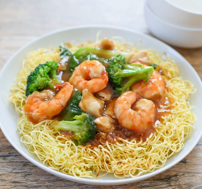 a close-up of crispy pan-fried noodles with shrimp and sauce