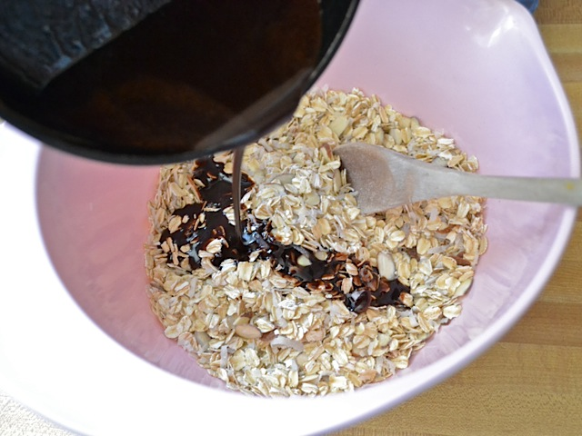 chocolate mixture being poured over oats into mixing bowl