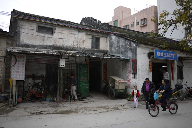 woman riding bicycle by older buildings in Nanping, Zhuhai, China
