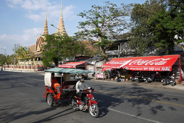 ma driving a tuk-tuk past the Cambodian Supreme Court building in Phnom Penh
