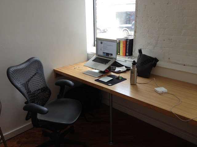 My desk at Studio Huddle, complete with a nice chair, laptop stand, and reference books!