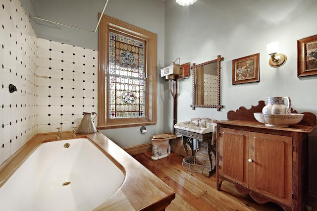 A reconstructed Victorian style bathroom with wooden floor and furniture, showing pitcher and bowl, 'modern' decorated handbasin (lavatory). Thomas Crapper equipped decorated toilet installed!