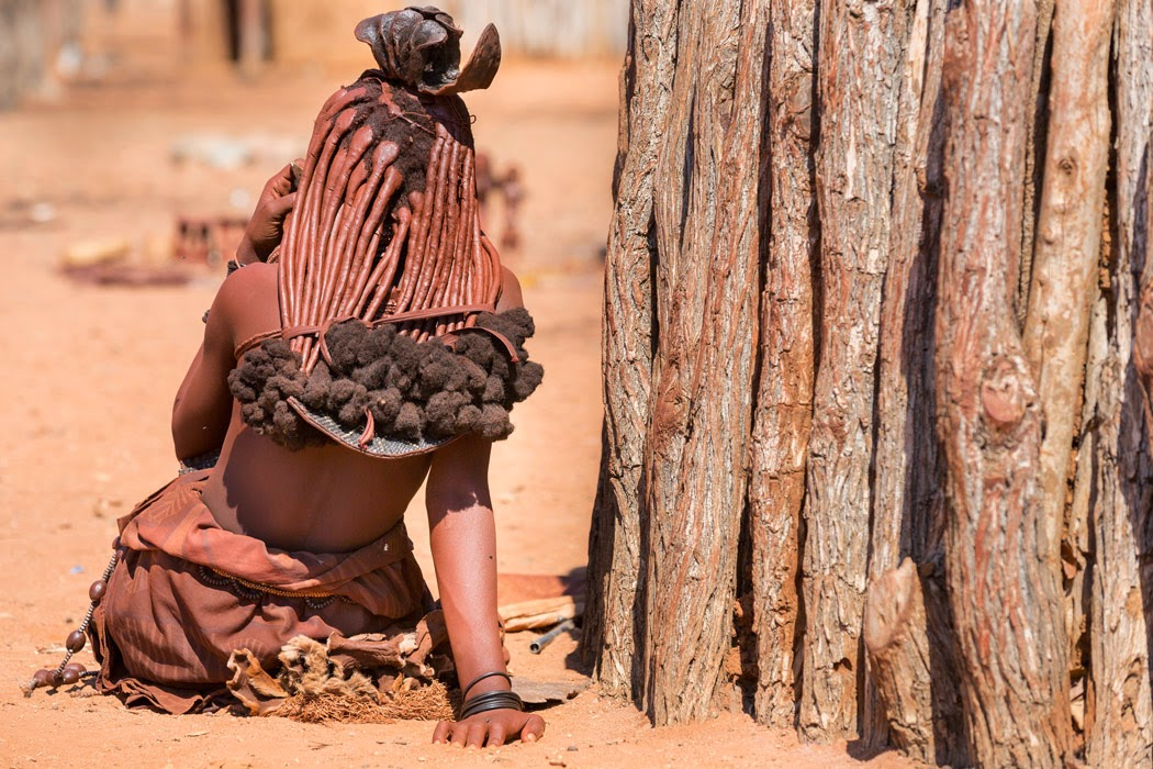 Namibian woman sitting under a three