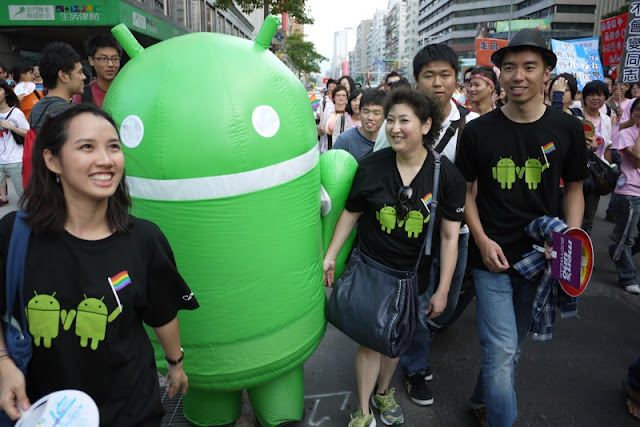 Person in an Android Robot suit and others wearing shits with two Android Robots holding hands and a rainbow flag