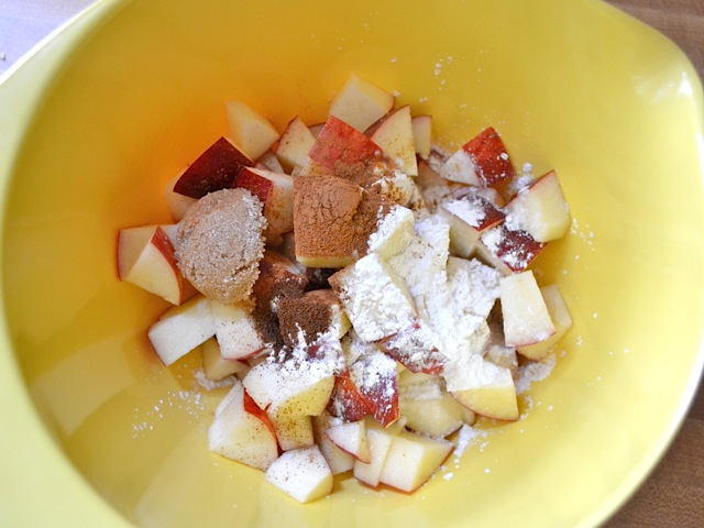 Chopped apples and seasoning in mixing bowl