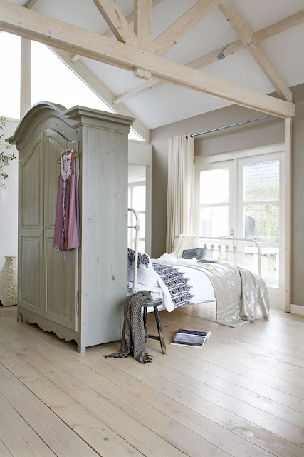 wardrobe works well as a room divider in large loft style bedroom