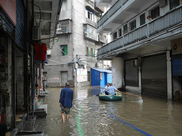 chengguan rowing a raft in a flooded street in Hunan